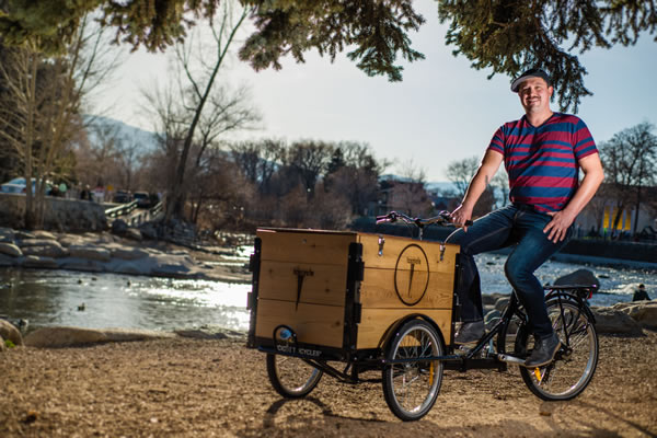 A man in a striped shirt riding a custom cedar box ice cream bike / trike in a park by a creek.