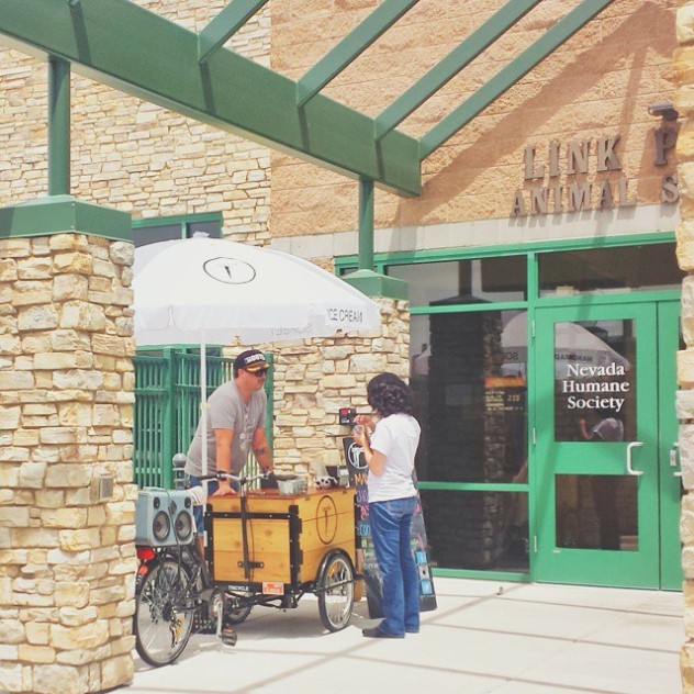 A barista is serving a customer from a custom cedar box coffee bike parked in front of the humane society