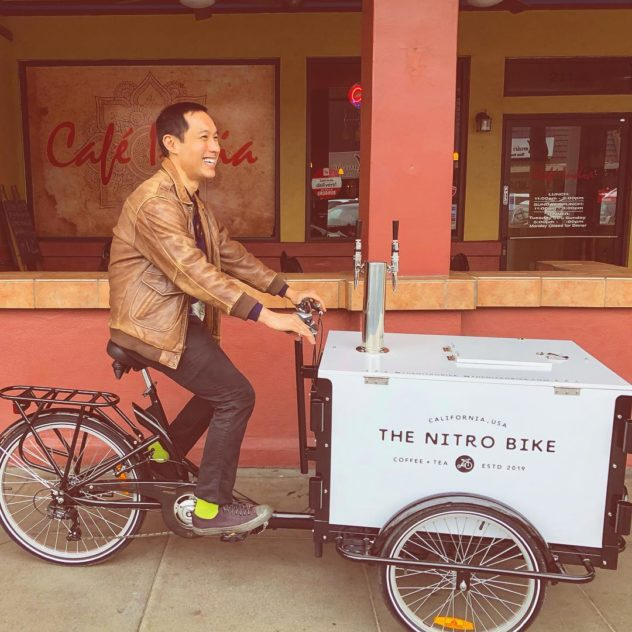 smiling man riding a custom graphic wrapped cold brew coffee bike on side walk