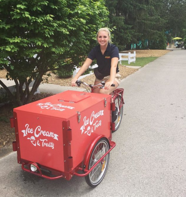 Woman riding a custom branded vinyl wrapped ice cream bike down the street in Vancouver.