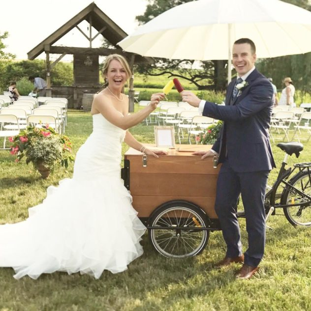 bride and groom cheers popsicles in front of a stained cedar wood box ice cream bike at a wedding