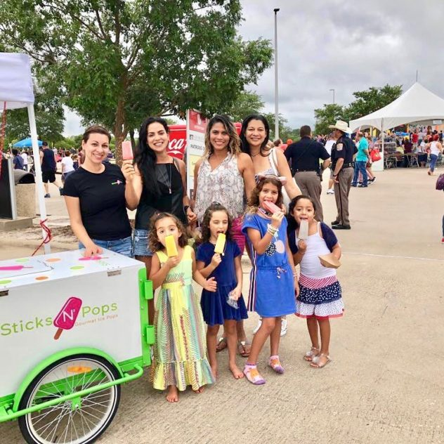 A group of happy people eating popsicles next to a A Popsicle Ice Cream Cart at a popup event