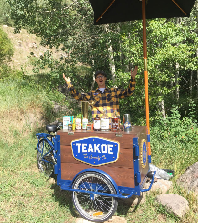 A blue frame cedar wood beverage cart bike in the woods