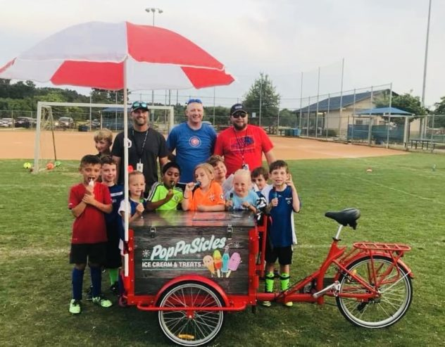A custom wrapped branded ice cream bike with an umbrella on a baseball field surrounded by athletes young and old!