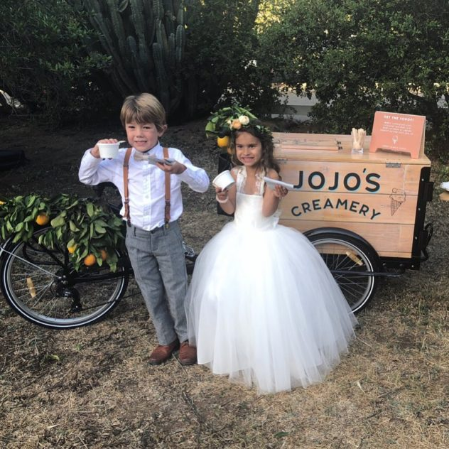 Youths enjoying ice cream dressed up for a wedding in front of a jojo's creamery branded ice cream bike / cart