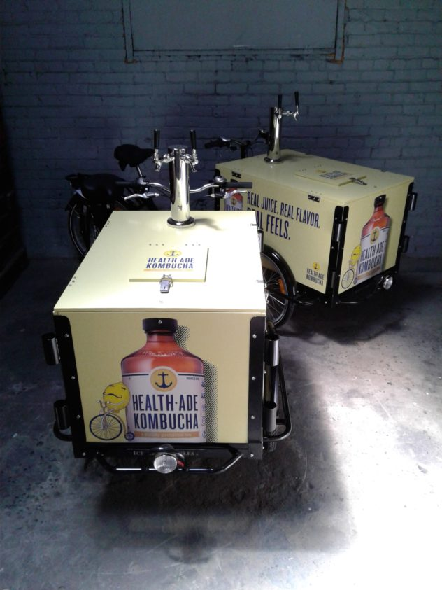 two custom wrapped yellow and black health-ade branded beverage bike carts with tap towers
