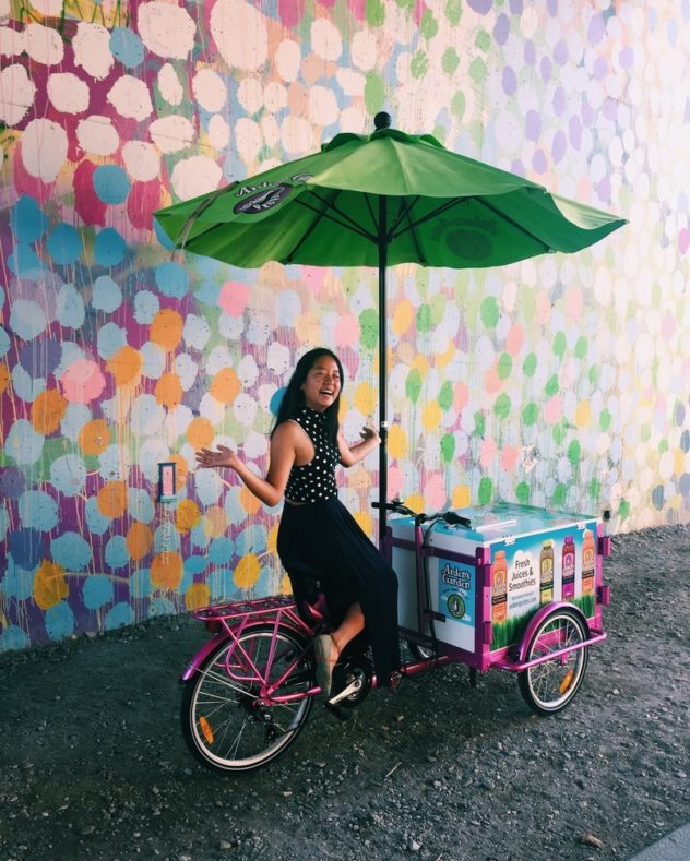 pink custom wrapped branded juice marketing bike with and umbrella being ridden with no hands down an alley with a mural