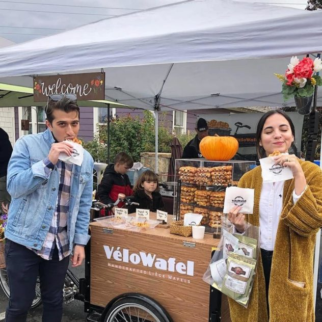 a couple eat waffles at a famers market in front of a food vendor stand with an ice cream bike food cart branded for velos waffles