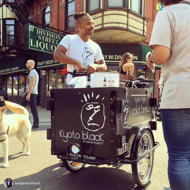 barista serving coffee in a town square from an Icicle Tricycles Cold Brew Coffee Bike