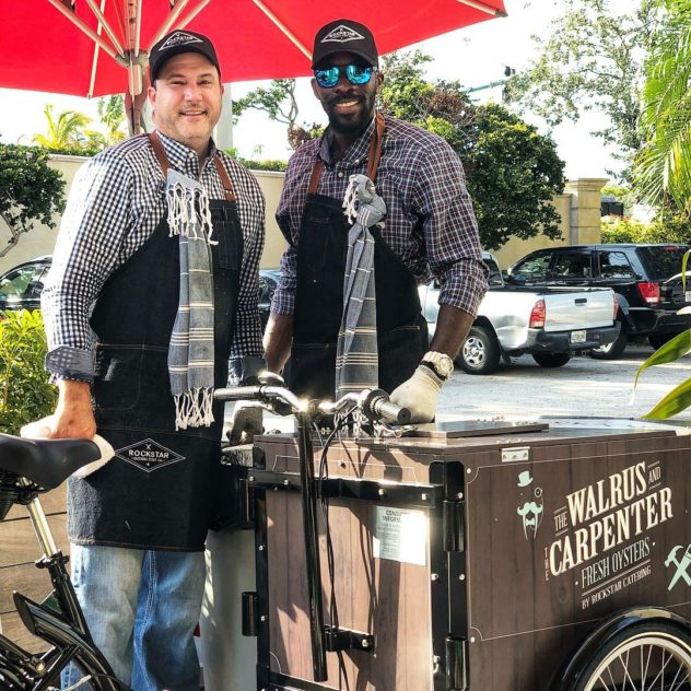 Two Rockstar caterers with faux wood vinyl wrap The Walrus and carpenter oyster Icicle Tricycles Ice Cream Bike Vending cart on a sunny day