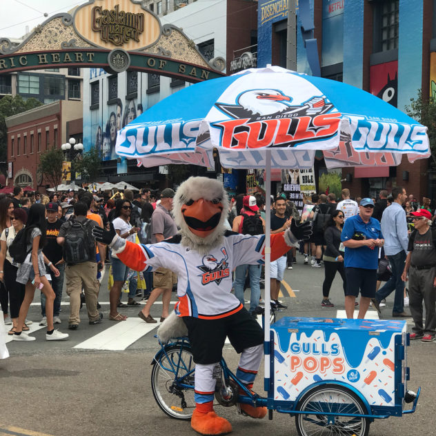A gulls sports mascot in a crowded street posing victoriously with a branded Icicle Tricycles Ice Cream bike