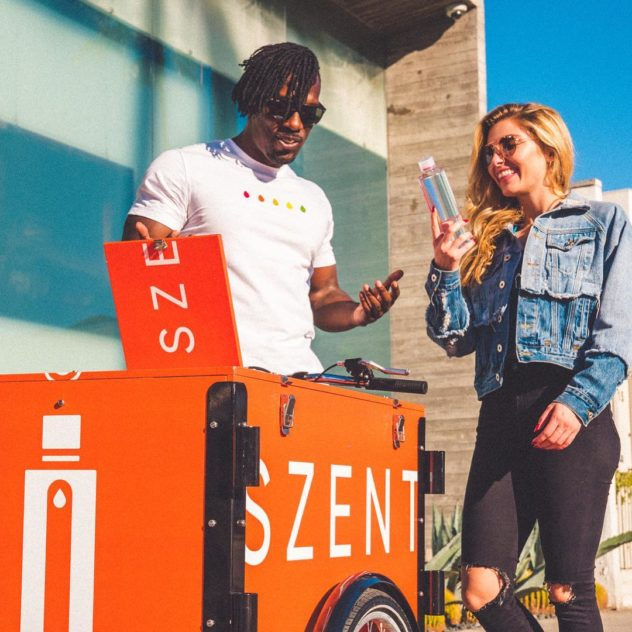 two models posing with a Szent Branded outdoor advertising bike