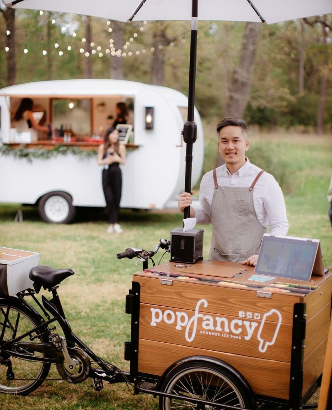 man posing with Popfancy cedar wood ice cream bike in front of a food cart