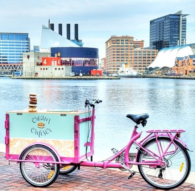 a custom wrapped icicle tricycle ice cream bike parked next to the water in Baltimore Maryland