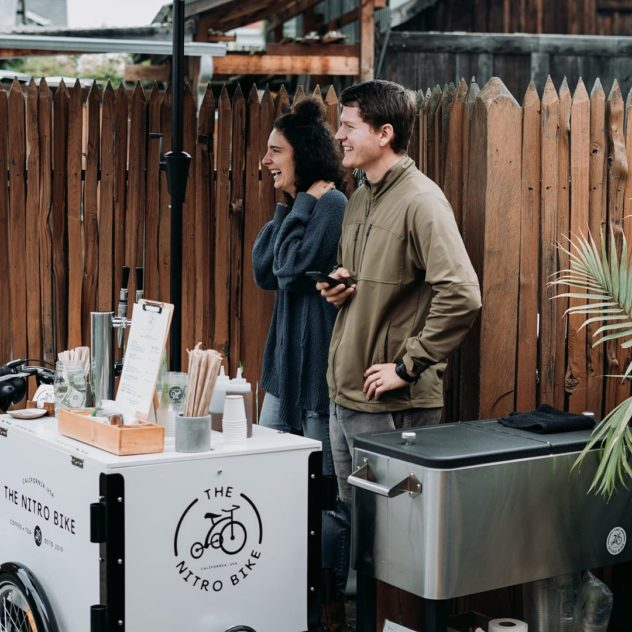 Alex & Erin Pujol catering cold brew in a back yard from The Nitro Bike icicle tricycles cold brew coffee bike barista cart