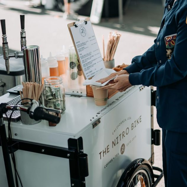 The Nitro Bike branded Icicle Tricycle Cold Brew Bike Coffee Cart in full operation at a mobile cold brew coffee business