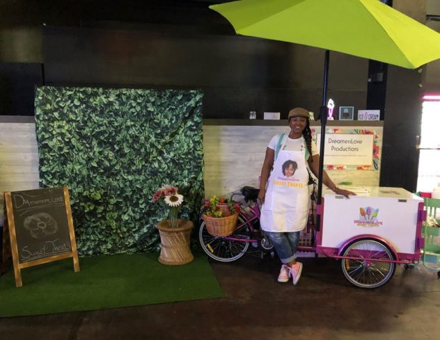Tee Brantly smiling on her pink Dreamers love branded Icicle Tricycle Ice Cream Bike cart with umbrella parked at a catering event