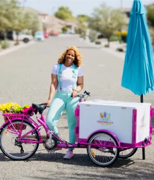 Tee Brantly smiling on her pink Dreamers love branded Icicle Tricycle Ice Cream Bike with umbrella parked on the street