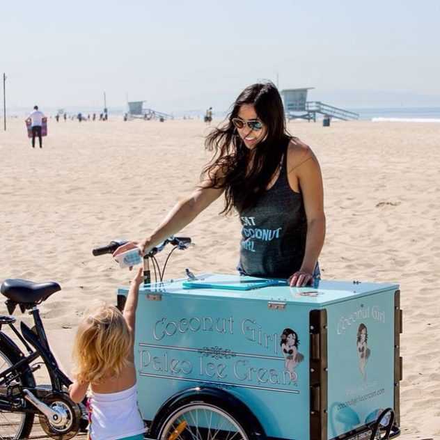 woman handing out popsicles coconut girl, popsicles on the beach trike. Vending bike.